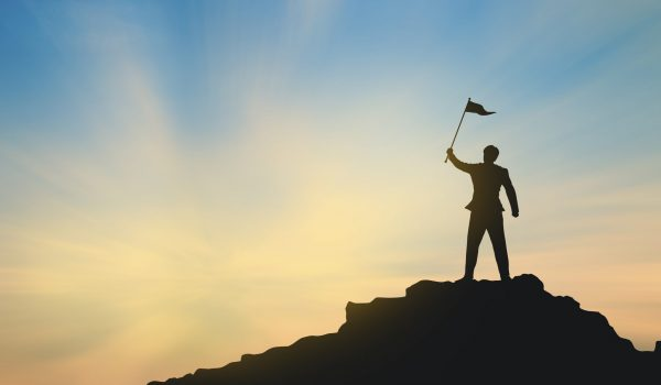 silhouette of man on mountain top over sky and sun light background,business, success, leadership, achievement and people concept